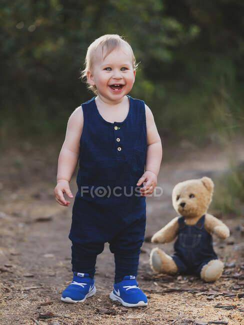 Allegro bambino in piedi a orso giocattolo in denim vestiti in natura. — Foto stock