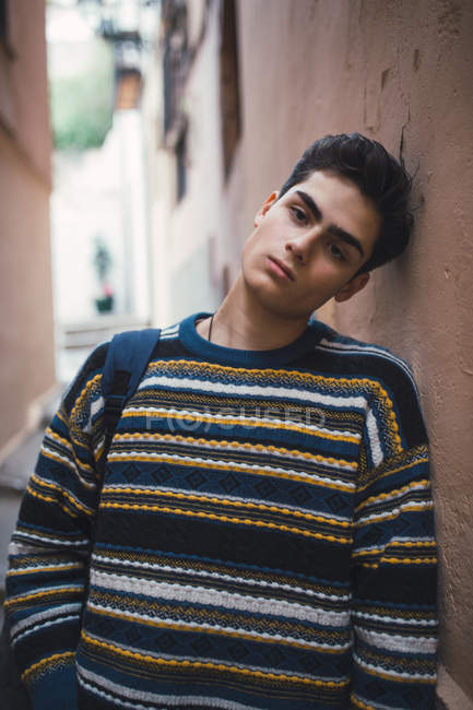Young confident teenager in sweater standing on city street and looking at camera. — Stock Photo