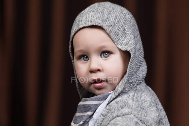 Portrait of adorable little toddler looking at camera on gray background. — Stock Photo