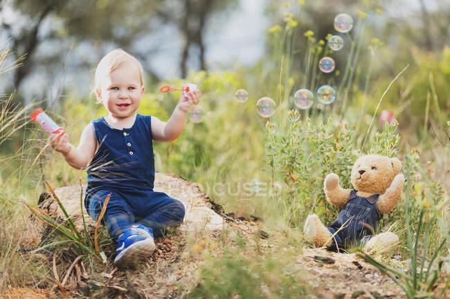Веселий маленький хлопчик, що стоїть біля іграшки з ведмедем у чорному одязі.. — стокове фото