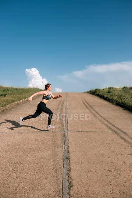 Sporty young woman running on hill outdoors — Stock Photo