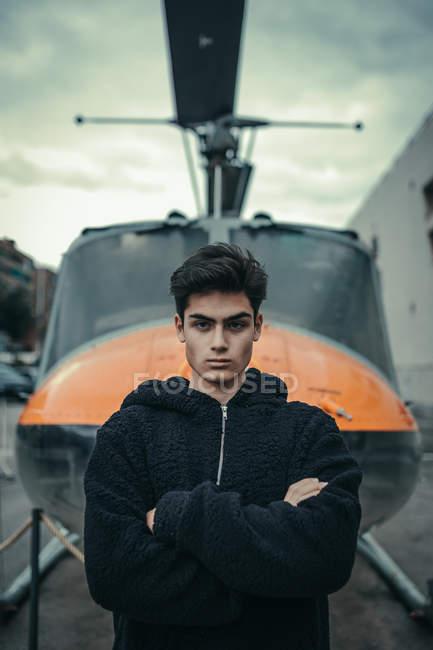 Молодой человек стоя с оружием, пересекли с вертолет памятник на фоне — стоковое фото