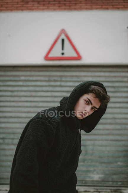 Продуманий підліток у чорний жакет з капюшоном, стоячи на вулиці з знак оклику і дивлячись на камеру — стокове фото