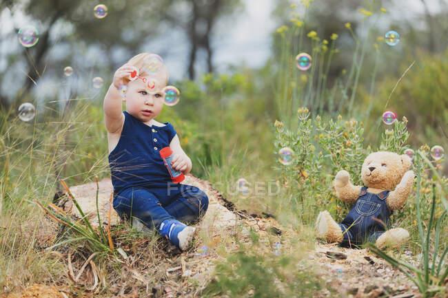 Alegre niño de pie en oso juguete en ropa de mezclilla en la naturaleza. - foto de stock