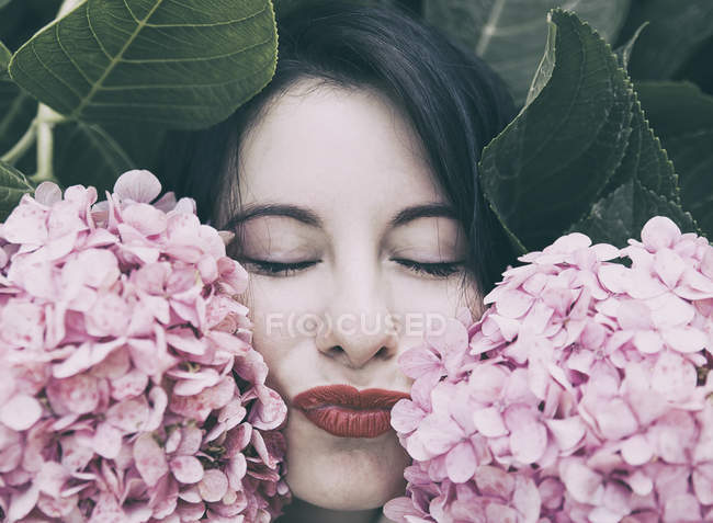 Portrait of young brunette woman with makeup in pink flowers — Stock Photo