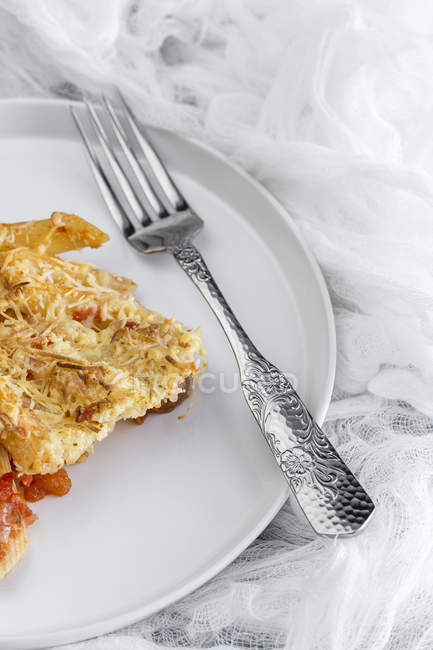 Macaroni with cheese and chorizo on white plate with fork — стоковое фото