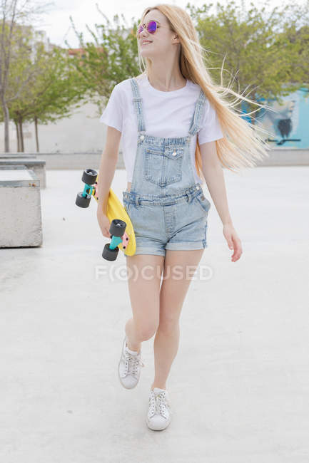 Blonde stylish girl with penny board walking in park — Stock Photo