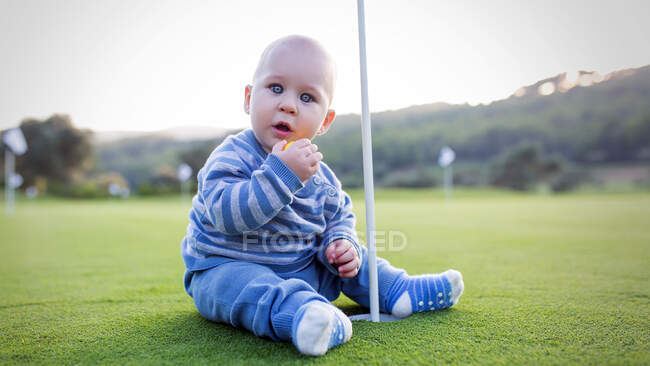 Young boy sitting on green lawn at the hole in golf club and looking at camera. — Stock Photo