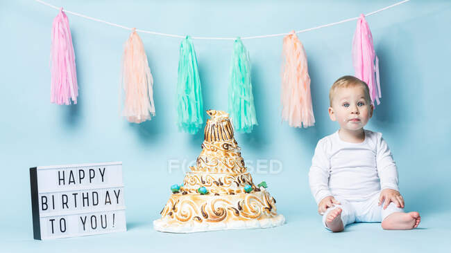 Cute little boy sitting at birthday cake and eating it with hand on blue background. — Stock Photo