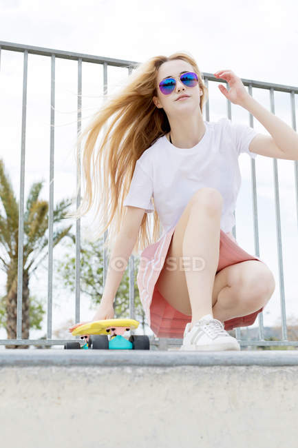 Blonde stylish girl in sunglasses sitting in skate park with penny board — Stock Photo