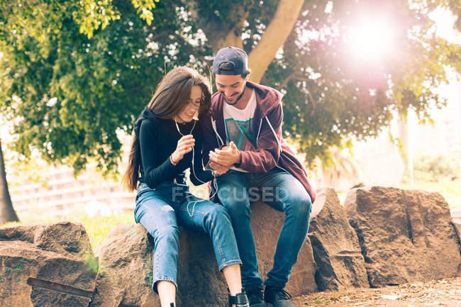 Улыбающаяся молодая пара сидит на скале со смартфоном в парке — стоковое фото