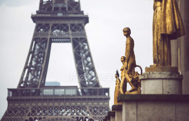 Gold covered statues of people on background of Eiffel Tower, Paris, France — Stock Photo