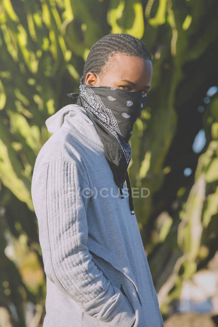 Cool ethnic man in do-rag and hoodie looking at camera against green plants — Stock Photo