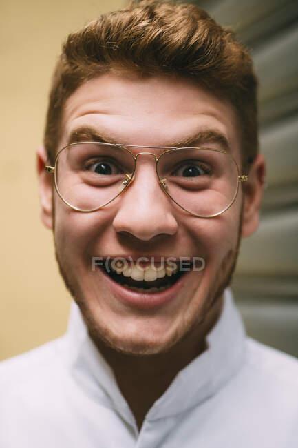 Gros plan de l'homme rousse lumineux joyeux dans des lunettes élégantes regardant la caméra avec excitation. — Photo de stock