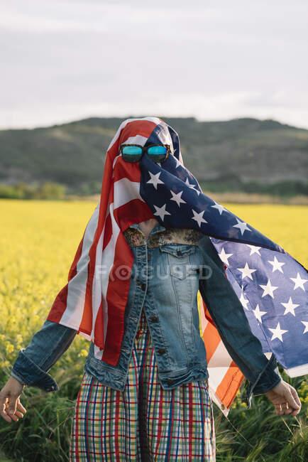 Леди в повседневной одежде в желтом поле в солнечных очках над американским флагом с солнечным светом — стоковое фото