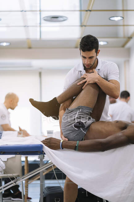El fisioterapeuta que trata a un hombre usando equipos para radioterapia - foto de stock