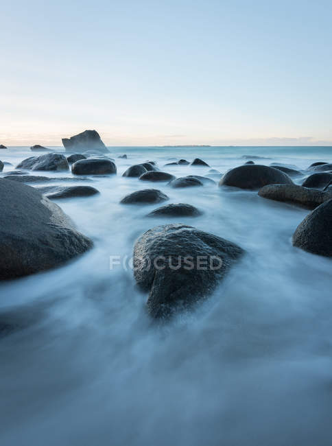 Smooth rocks in flow of water under blue sky — Stock Photo
