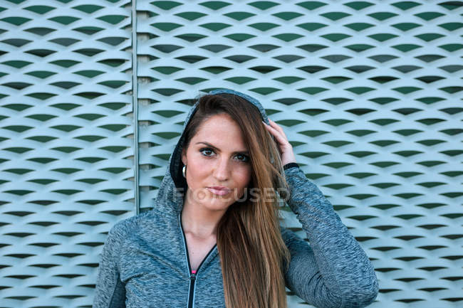 Portrait of young woman in sports clothes standing in front of blue net — Stock Photo