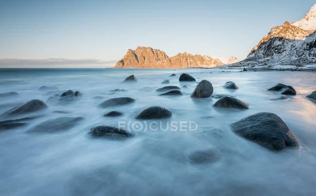 Гладкие темные камни в течение длительного потока воды на фоне скал, Лофотен, Норвегия — стоковое фото