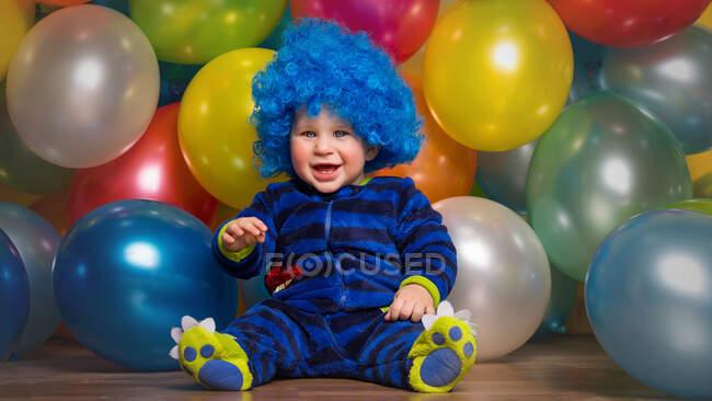 Criança adorável em peruca azul sentado no fundo de balões multicoloridos. — Fotografia de Stock