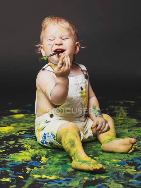 Adorabile sporco bambino seduto e giocare con vernice gialla e blu su sfondo scuro. — Foto stock