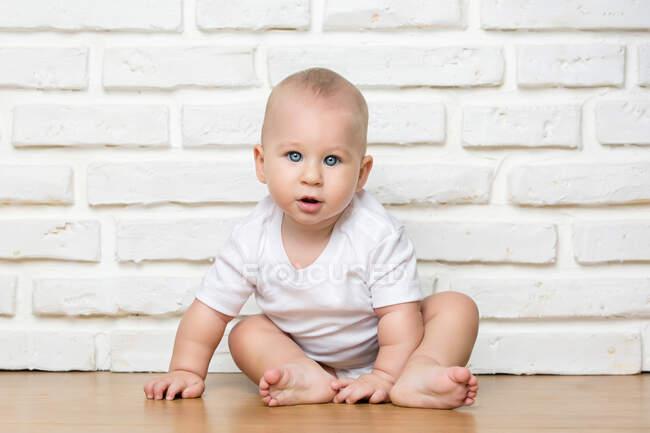 Cute toddler boy sitting at white brick wall and looking at camera. — Stock Photo
