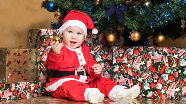 Портрет щасливі маленький хлопчик в костюмі Діда Мороза сидять на ялинку і проведення дрібничка — стокове фото