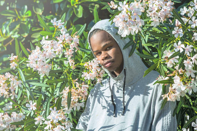 Cool ethnic man in hooded jacket standing in nature — Stock Photo