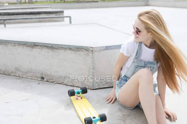 Blonde funky girl sitting on floor with penny board — Stock Photo