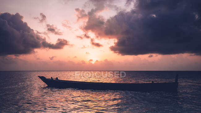 Empty boat floating in ocean under cloudy sky and sunset. — Stock Photo