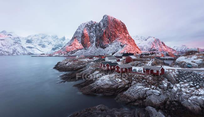 Malerische Aussicht auf Dorf mit roten Holzhäusern auf felsigen Küste auf ruhiger See Hafen mit Bergen, Lofoten, Norwegen — Stockfoto