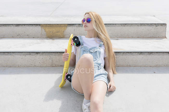 Blonde funky girl in sunglasses leaning on stairs sitting with penny board outdoors — Stock Photo