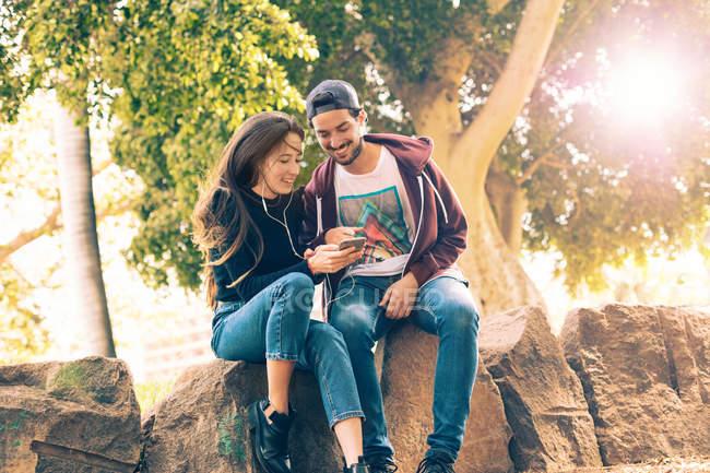 Смеющаяся молодая пара сидит на скале со смартфоном в парке — стоковое фото