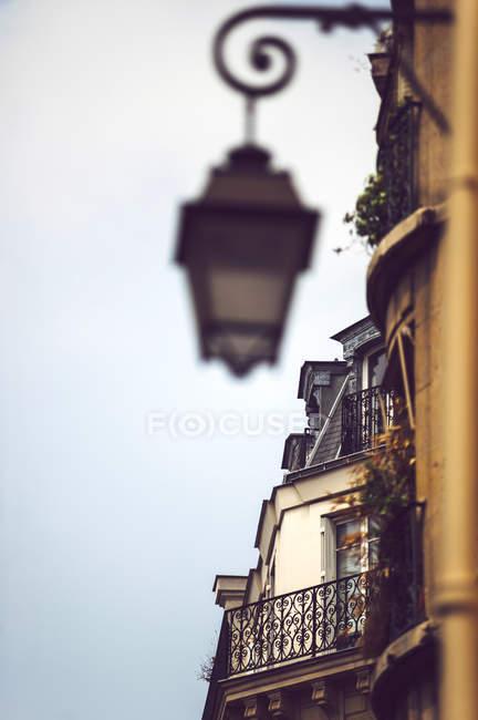 Primer plano de la fachada del edificio con linterna borrosa colgando en la pared, París, Francia - foto de stock