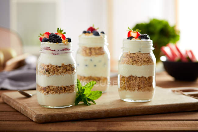 Vasetti di vetro con muesli e yogurt sul bordo di legno — Foto stock