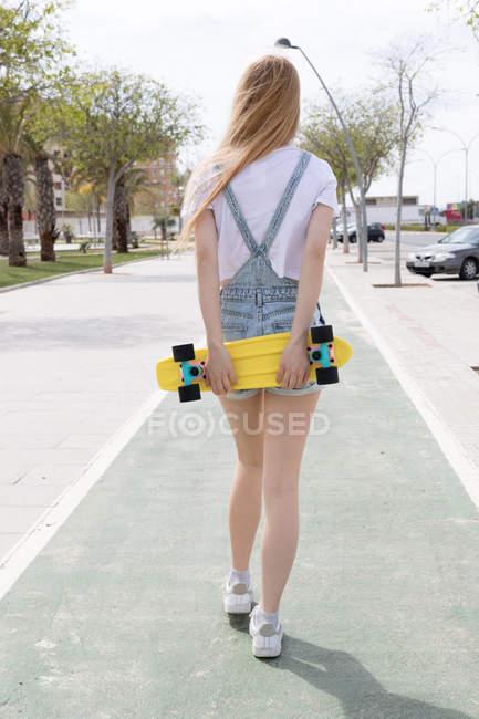 Блондинка стильная девочка ходит по улице с пенни-доской — стоковое фото