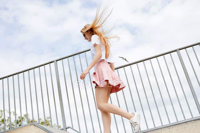 Улыбающаяся блондинка с длинными волосами, идущая перед металлическим забором — стоковое фото