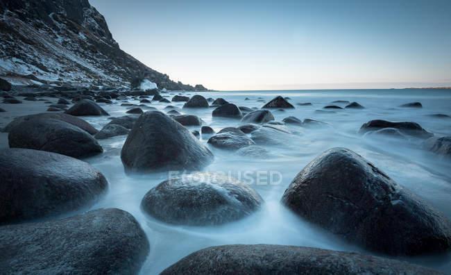 Rocce lisce nel flusso dell'acqua sotto il cielo blu — Foto stock