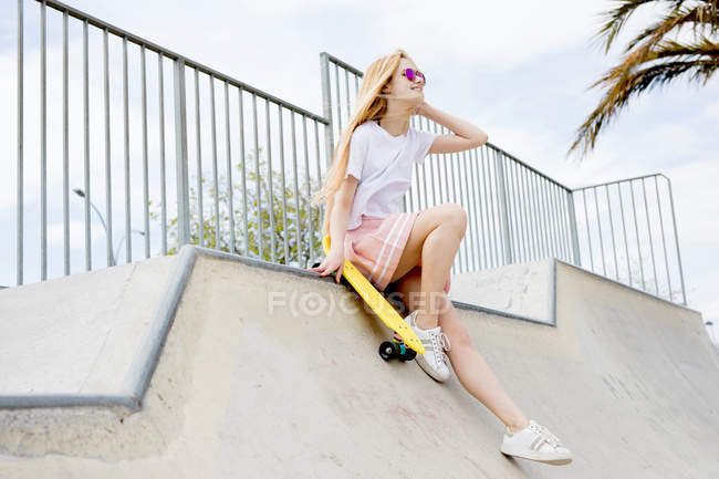 Smiling stylish blonde girl in sunglasses with penny board in skate park — Stock Photo