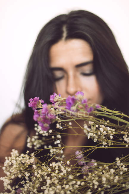 Blooming flowers and sensual young woman on background — Stock Photo