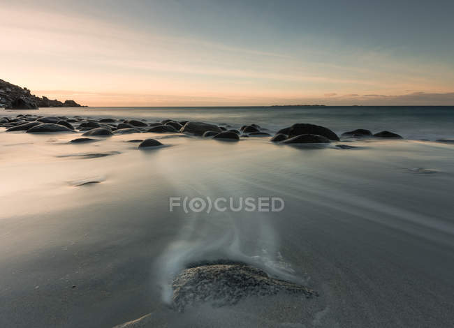 Smooth rocks in flow of water under sunset sky — Stock Photo