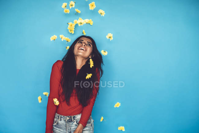 Молодая женщина стоит и бросает цветы на голубом фоне — стоковое фото