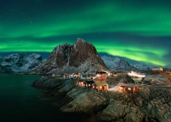 Illuminato pittoresche case rosse sulla riva remota in montagna sotto l'aurora boreale di notte — Foto stock
