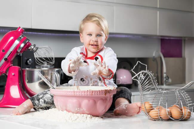 Маленький мальчик сидит на грязном столе с котом и играет с ингредиентами для приготовления пищи. — стоковое фото
