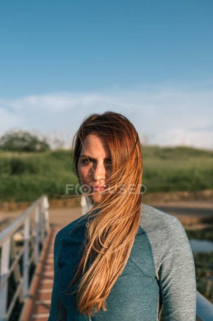 Портрет привлекательной спортивной молодой женщины, стоящей на пирсе на природе — стоковое фото