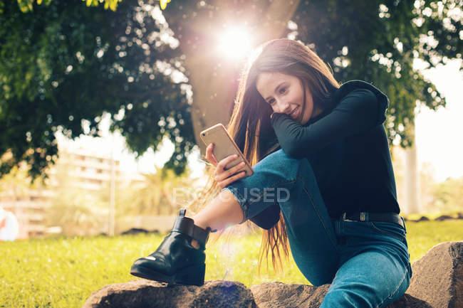 Mujer sonriente joven sentada en la roca y usando el teléfono inteligente en el parque - foto de stock
