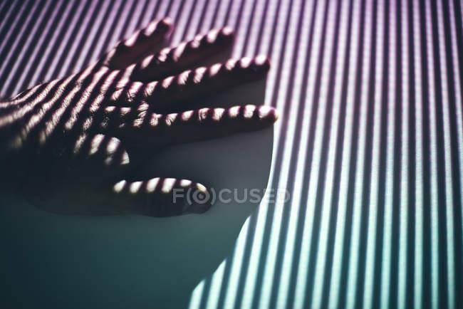 Крупный план женской руки на поверхности с полосатой тенью — стоковое фото