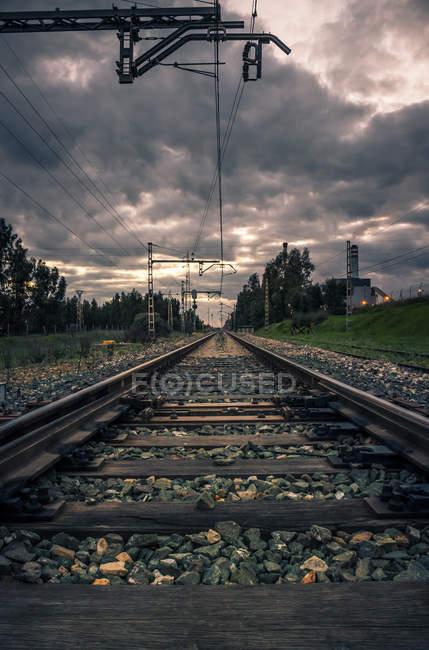 Вид на железную дорогу, бегущую в сельской местности с темными тучами над головой — стоковое фото