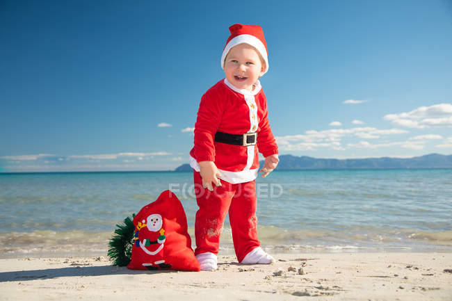 Cheerful little boy in Santa Claus costume standing on beach in sunny day — Stock Photo