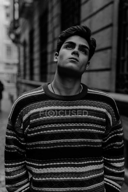 Young confident teenager in sweater standing on city street and looking up — Stock Photo